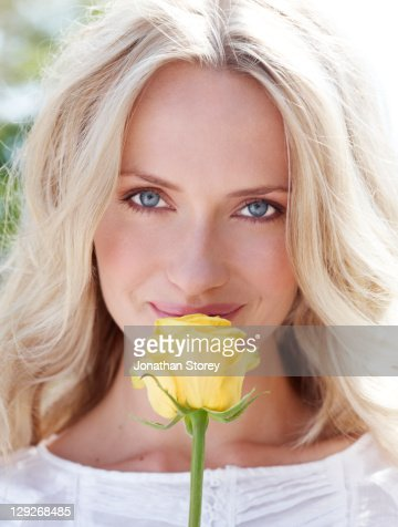 Female outside smelling yellow rose : Stock Photo
