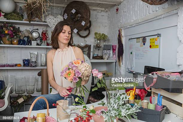Female owner making flower bouquet at store