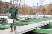 Portrait of female owner on sturgeon farm feeding fish