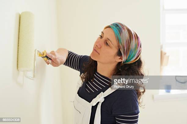 Female painter and decorator painting with roller