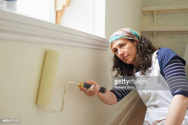 Female painter and decorator using paint roller