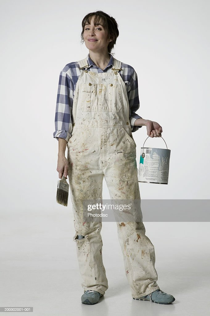 Female painter in overalls holding brush and paint bucket : Stock Photo