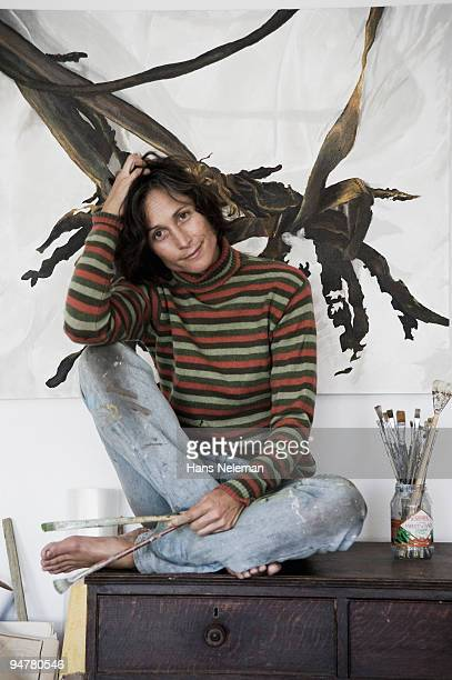 Female painter with paint brushes sitting on a table and smiling