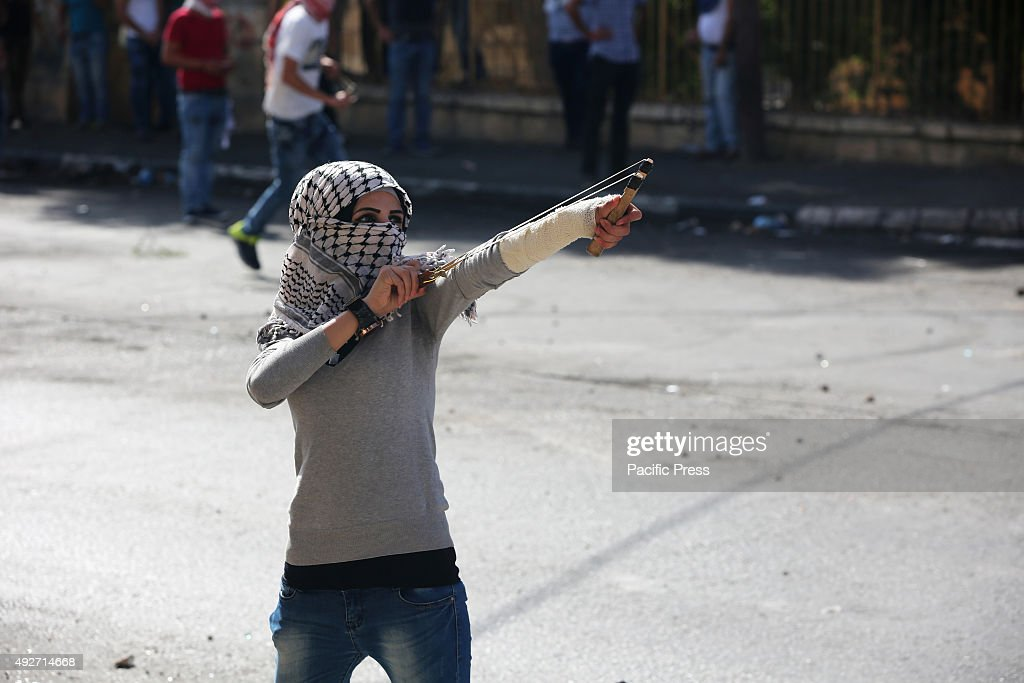 A female Palestinian demonstrator is seen using a slingshot against Israeli soldiers during clashes in the West Bank city of Bethlehem Following the...
