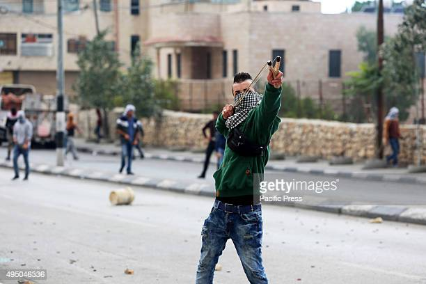 A female Palestinian demonstrator is seen using a slingshot against Israeli soldiers during clashes in the West Bank city of Bethlehem Following...
