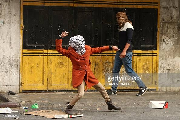 A female Palestinian demonstrator throws stones at members of the Israeli security forces during clashes in the centre of the West Bank city of...