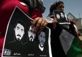 Female Palestinian protestors hold pictures of jailed Palestinian football player Mahmud Sarsak and prisoners Akram Rikhawi and Samir alBaraka during...
