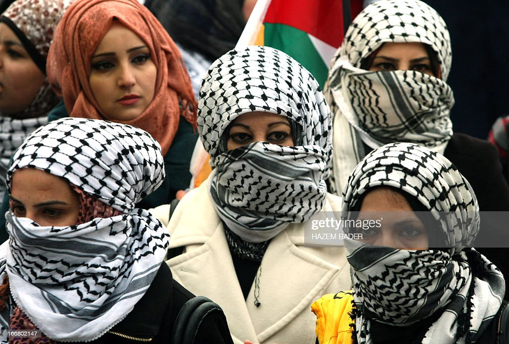 Female Palestinian students loyal to the Fatah movement, covering their faces with the keffiyeh, the signature headdress worn by the movement's late Palestinian leader Yasser Arafat, rally during their election campaign for the Student's Council, at Hebron University in the southern West Bank city of the same name, on April 17, 2013. The two main parties vying for seats are Fatah and the Islamic Hamas movement.