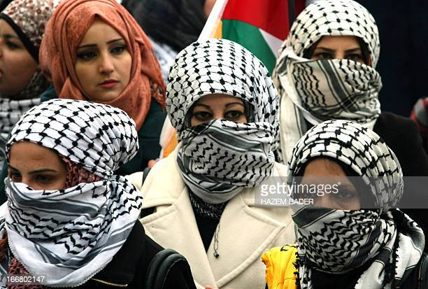 Female Palestinian students loyal to the Fatah movement covering their faces with the keffiyeh the signature headdress worn by the movement's late...