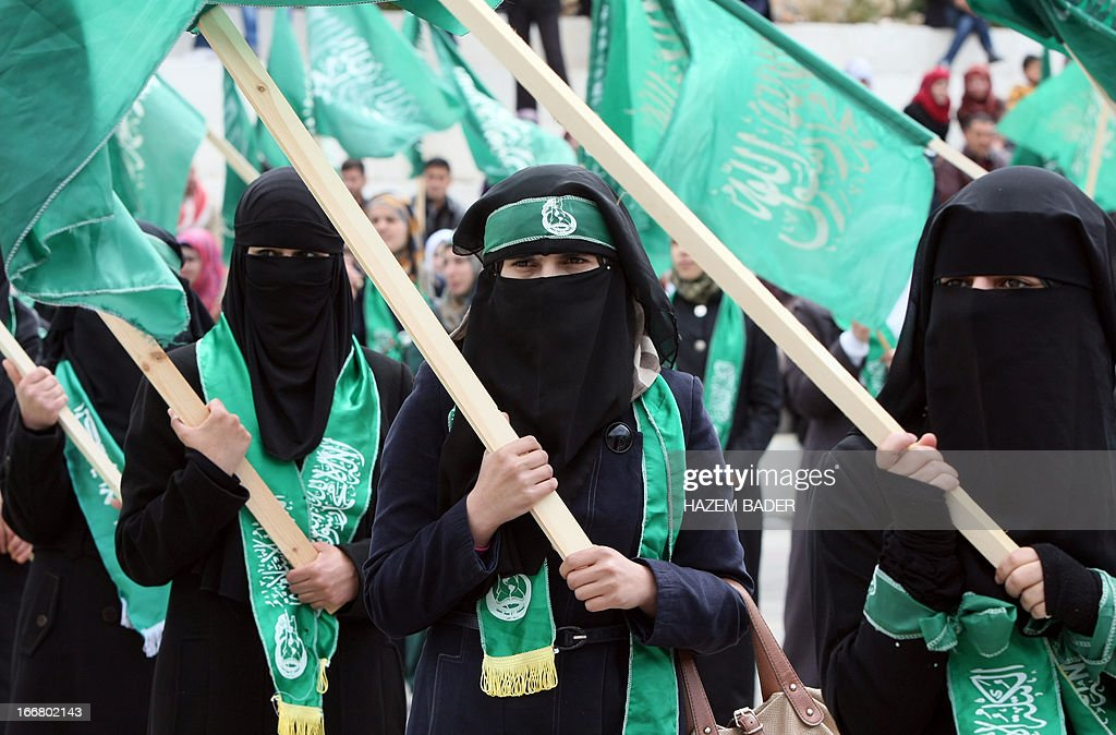 Female Palestinian students loyal to the Islamic Hamas movement, carry the movement's green flag, during their election campaign for the Student's Council, at Hebron University in the West Bank city of Hebron, on April 17, 2013. The two main parties vying for seats are Fatah, founded by the late Palestinian leader Yasser Arafat and the Hamas.