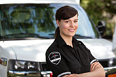 Portrait of a happy friendly female paramedic standing in front of ambulance