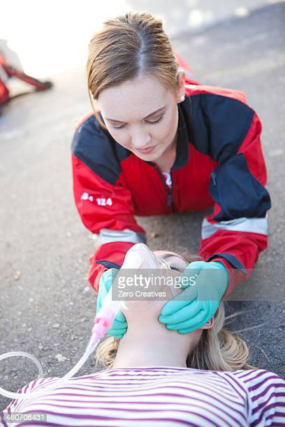 Female paramedic tending patient on road
