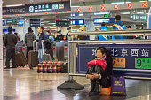A female passenger sits on her luggage in Beijing West Railway Station China's 40day spring travel rush called 'chunyunthe largest annual migration...