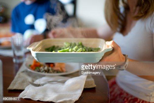 female passing green beans