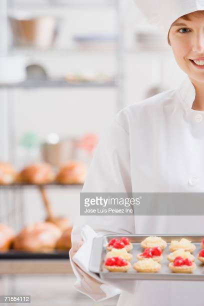 Female pastry chef with tray of tarts