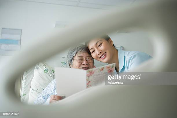 Female patient and her daughter reading a Get Well card viewed through a hole of a bed