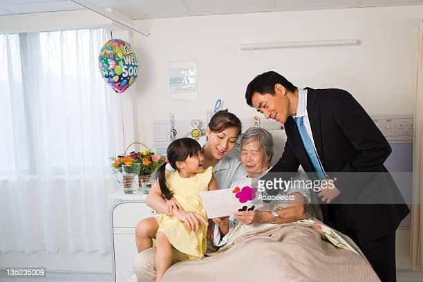 Female patient and her family looking at a Get Well card