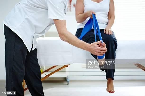 Female patient faire quelques exercices d'étirement de jambe