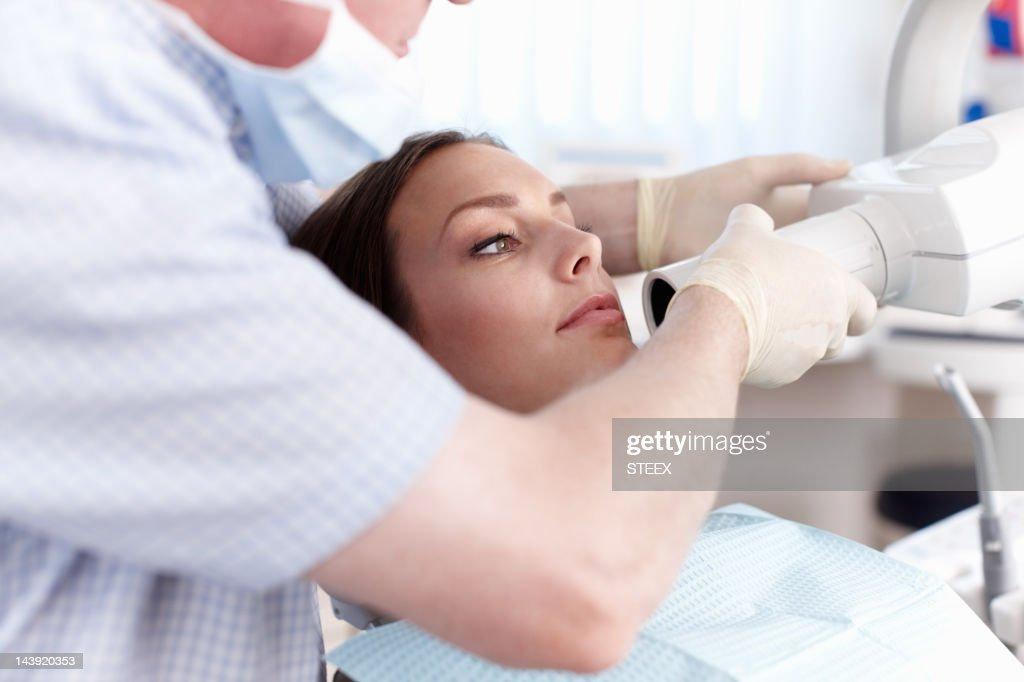 Female patient going through dental treatment : Stock Photo