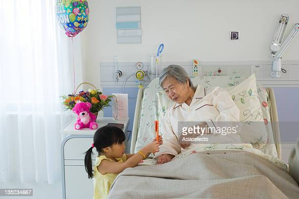 Female patient looking at her granddaughter holding a Get Well card