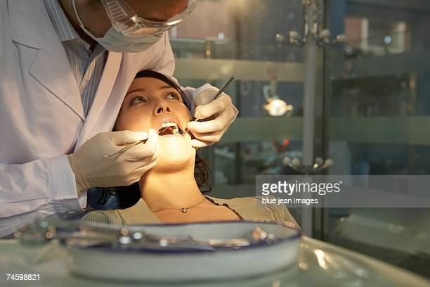 A female patient  opens wide while a male dentist cleans her teeth.
