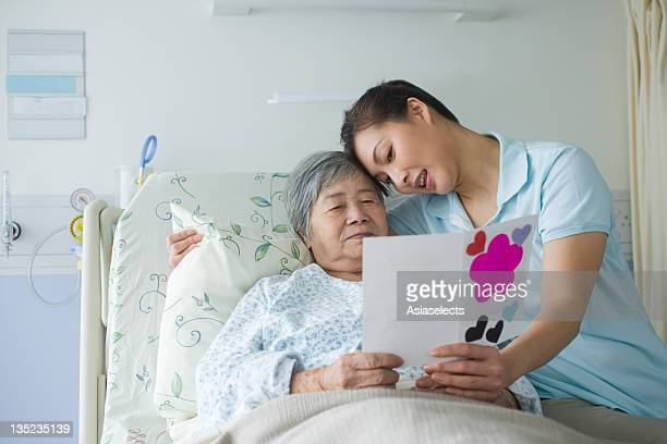 Female patient reading a Get Well card with her daughter sitting beside her