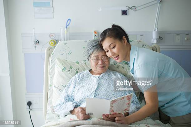 Female patient reading a Get Well card with her daughter standing beside her