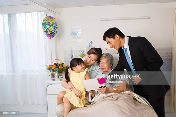 Female patient reclining on the bed and her family sitting beside her