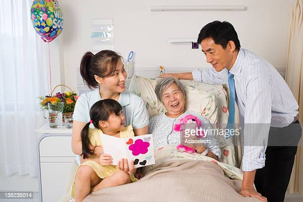 Female patient reclining on the bed and smiling with her family beside her
