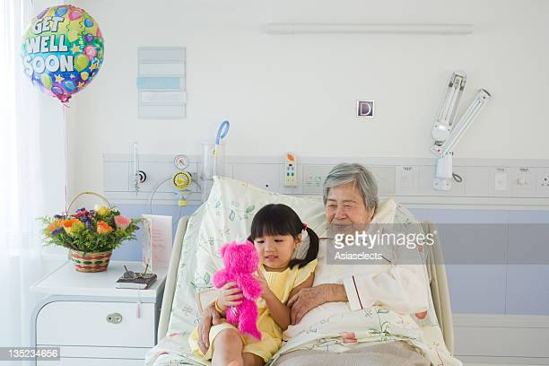 Female patient reclining on the bed with her granddaughter in the hospital