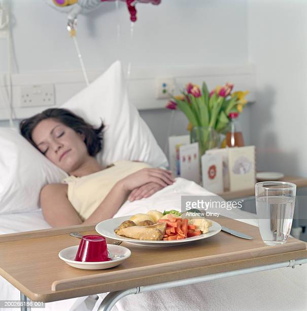 Female patient sleeping in hospital bed, meal on bedside table