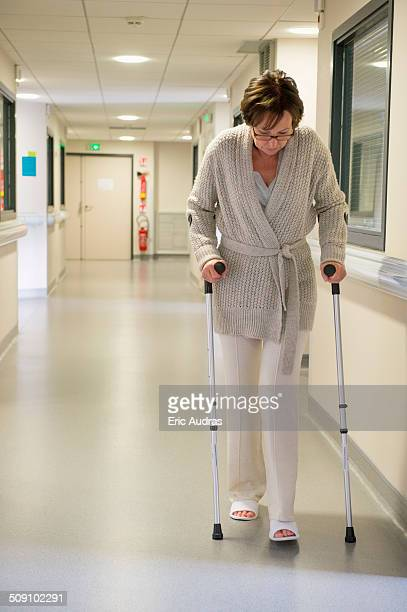 Female patient walking with the help of crutches