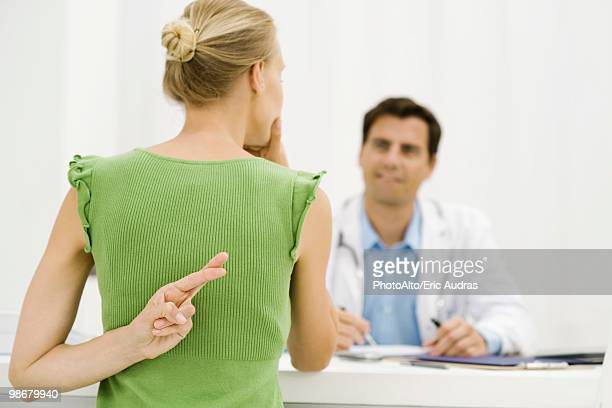 Female patient with hand behind back crossing fingers, speaking with doctor
