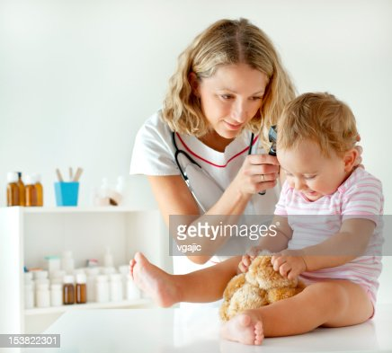 Female Pediatrician Doing Ear Exam of Baby Girl Patient : Stock Photo