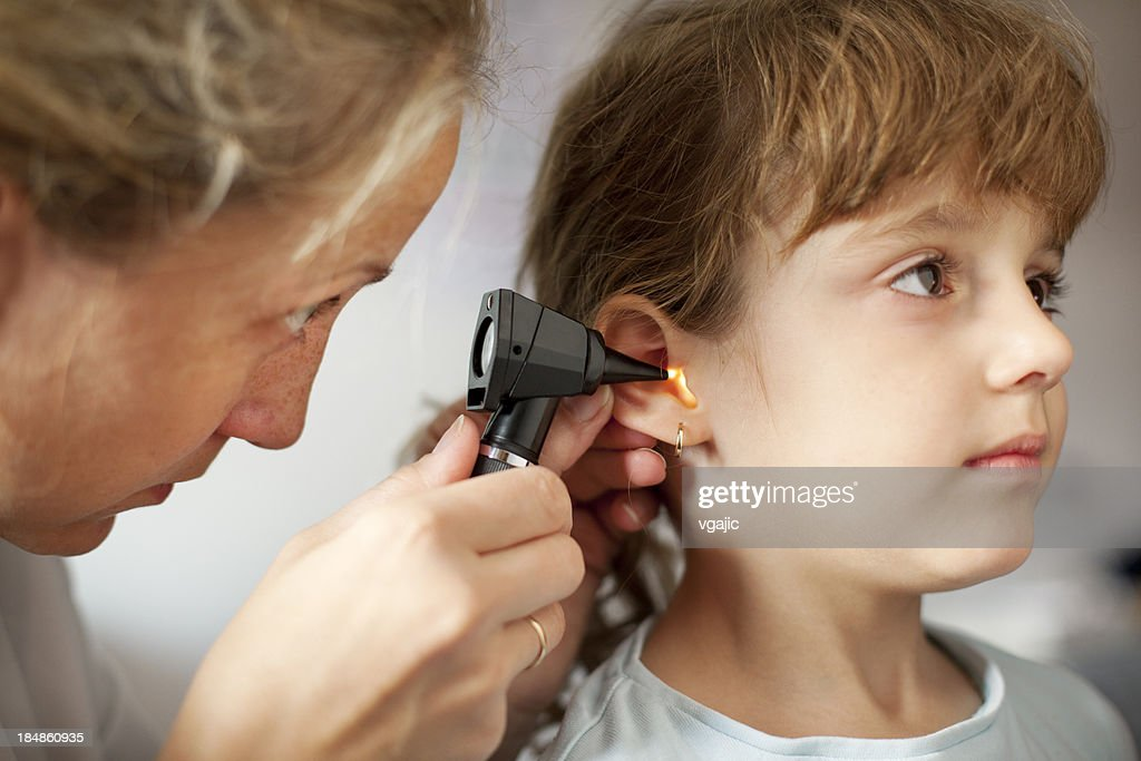 Female Pediatrician Doing Ear Exam of Little Girl Patient