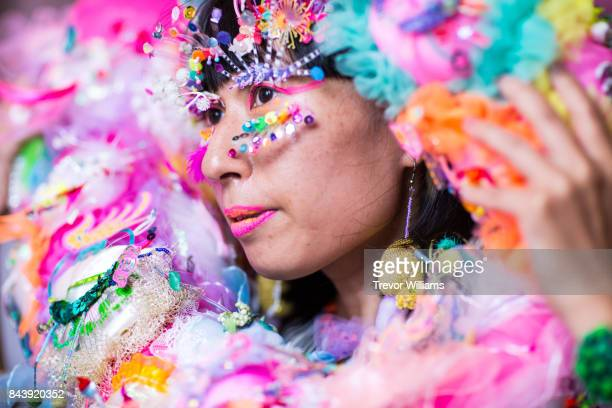 A female performance artist wearing a colorful hand made costume