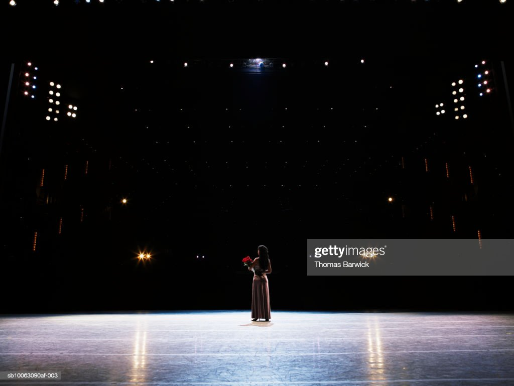 Female performer holding bouquet of roses on stage, rear view
