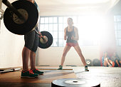 Female performing deadlift in warehouse gym.