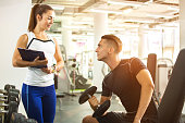Female personal trainer showing exercise report to her male client in a gym.