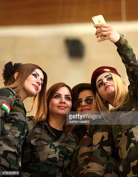 Female peshmerga fighters take a selfie in Arbil the capital of the Kurdish autonomous region in northern Iraq on June 9 2015 AFP PHOTO/SAFIN HAMED