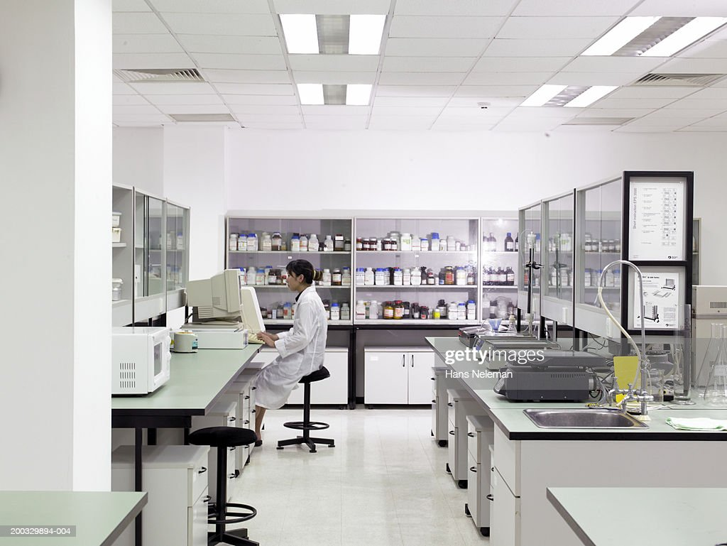 Female pharmaceutical worker in laboratory, side view : Stock Photo