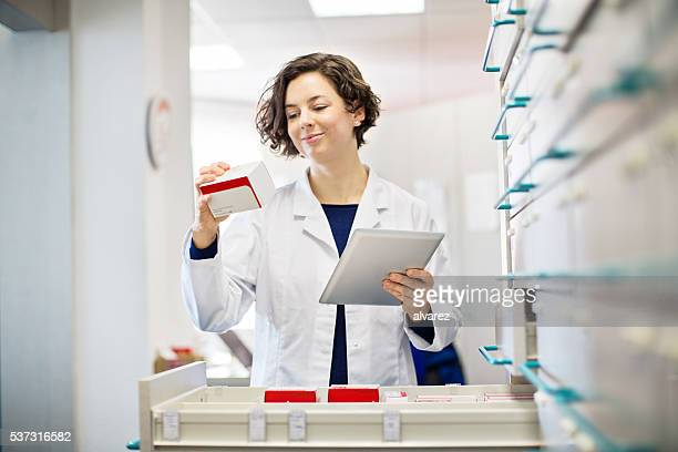 Female pharmacist checking information of medicine