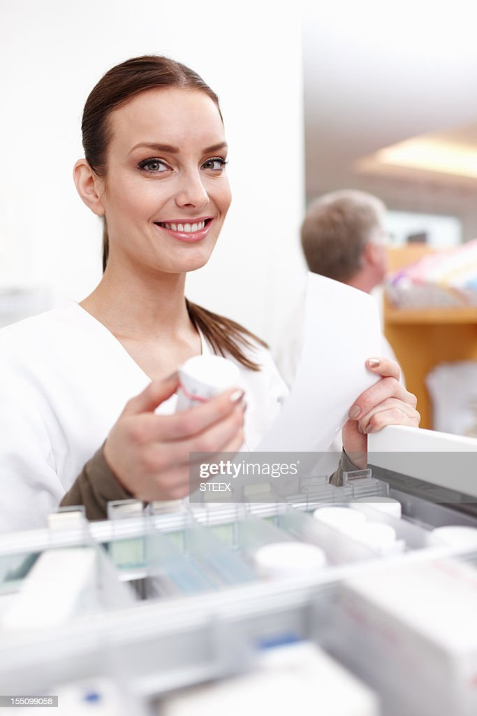 Female pharmacist checking medicine with colleague : Stock Photo