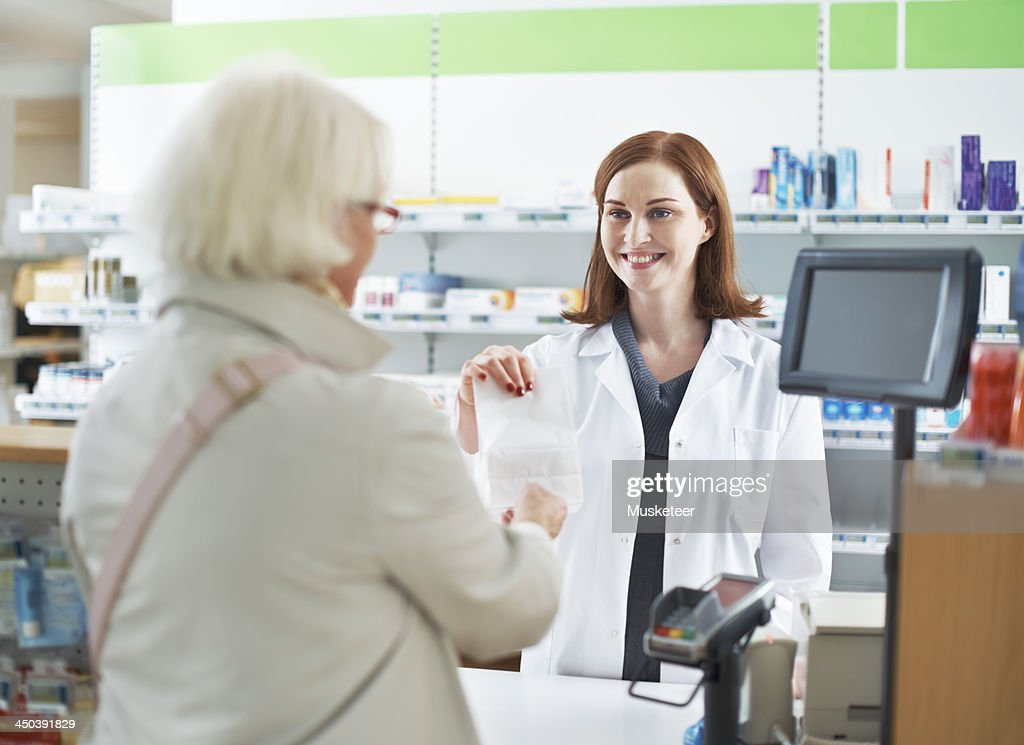 Female pharmacist giving package to customer : Stock Photo
