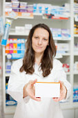 Female pharmacist holding a box of medications. Selective focus photograph, with focus on foreground.