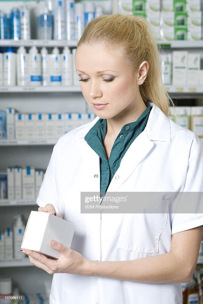 Female pharmacist looking at medicine in pharmacy : Stock Photo