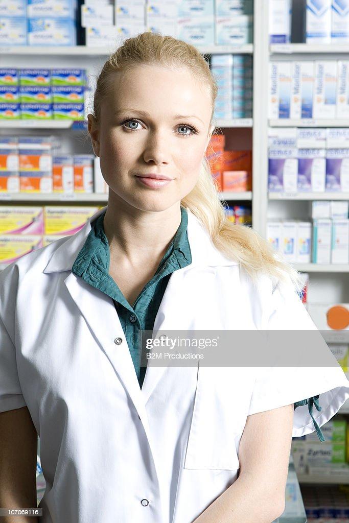Female pharmacist standing by shelves in pharmacy : Stock Photo