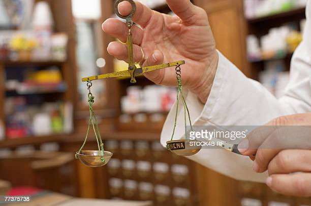 Female pharmacist using old fashioned scale to preparing drugs