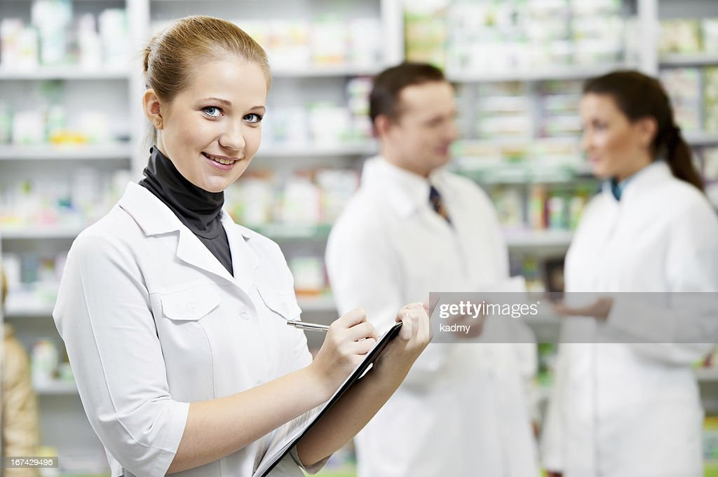 Female pharmacy technician with two others in background : Stock Photo