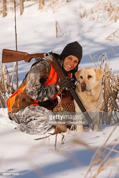 Female Pheasant Hunter In Winter With Yellow Lab